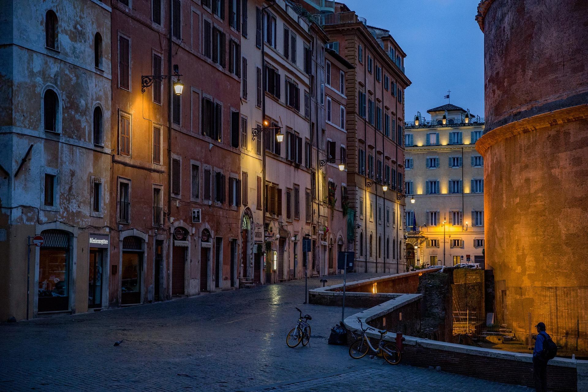 Foto da Rua Panteão em Roma. Rua estreita, à meia luz com prédios altos